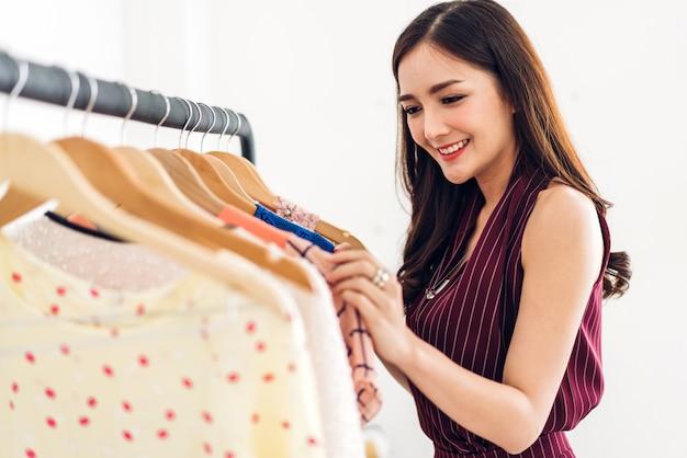 美しい若いアジア女性のショッピングとstore.fashionショッピング概念で服を選ぶ