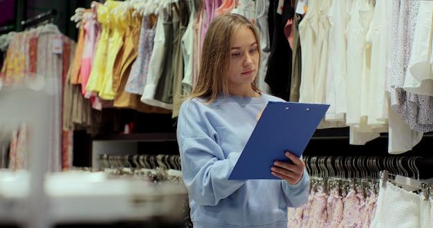 衣料品店の在庫をチェックする店長。中小企業の所有者が商品を注文します。