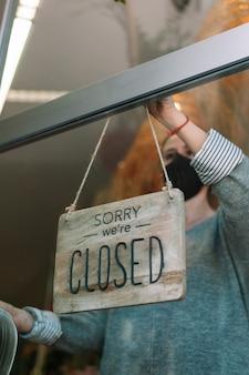 ドアガラスを通して開いたサインを大きく回し、サービスの準備ができているマスクを身に着けている店の所有者