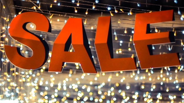Store sale sign. special offer banner with the red sale text gold bokeh blur background
