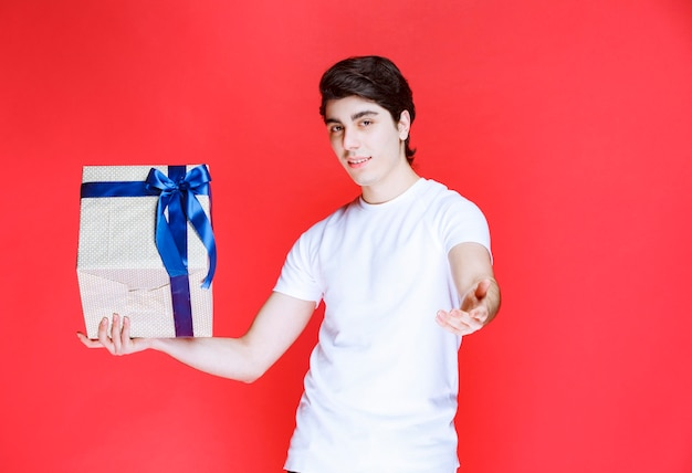Storeman holding a white gift box and asking for payment