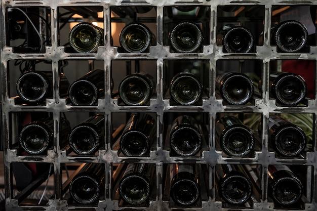 装飾的な金属製の棚にワインボトルを保管する