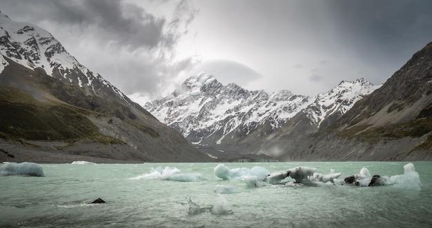 高山の地形の氷河湖に氷の破片が接近している嵐mtクックニュージーランド