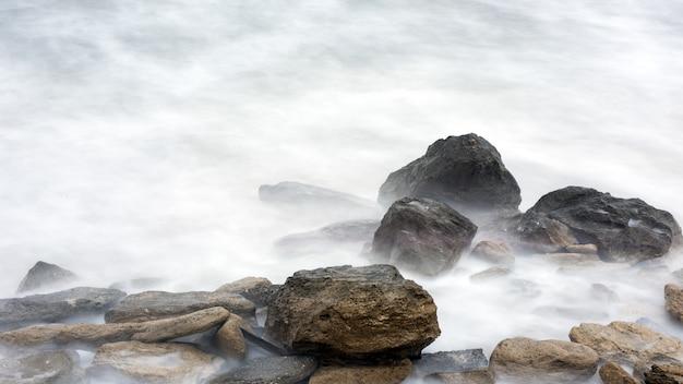 바다의 폭풍, 큰 거품 파도가 바위에 충돌