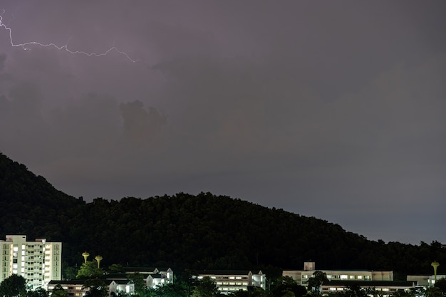 Storm lightning strikes in mountains during a thunderstorm at night. beautiful dramatic view