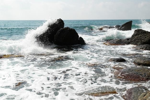 Буря на море. вода, камни и морская пена.