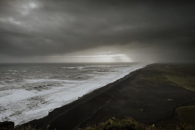 黒い砂のビーチに達する嵐
