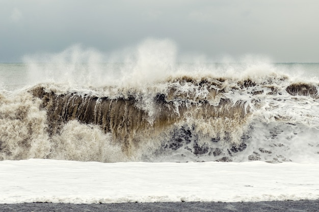 Storm on the sea - a big wave with sand and foam rises near the shore.