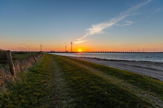 日没でオランダのゼーラント州の高潮障壁と風車