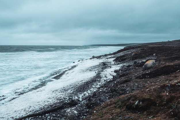 Storm on the white sea coast. waves with white foam roll on the rocky shore. polar wild landscape.