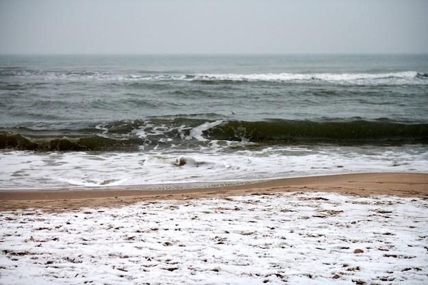 Бурный пейзаж зимы балтийского моря. бурлящие и пенящиеся морские волны и песчаный пляж, покрытый снегом. тишина и уединение.