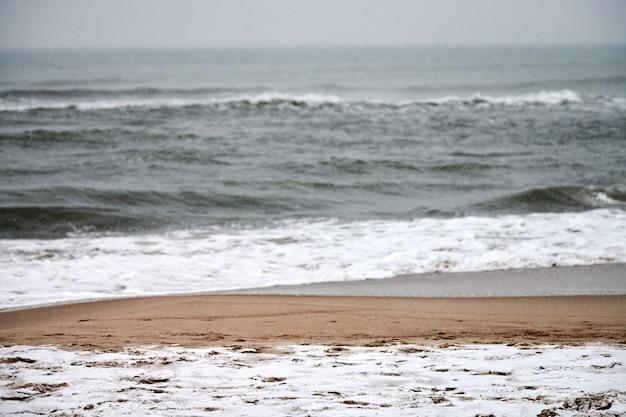 Бурный пейзаж зимы балтийского моря. бурлящие и пенящиеся морские волны и песчаный пляж, покрытый снегом