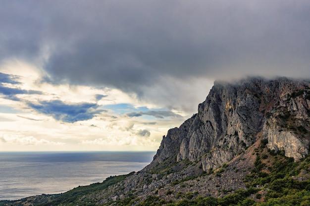 산과 해안의 바다 위에 폭풍우 치는 회색 구름