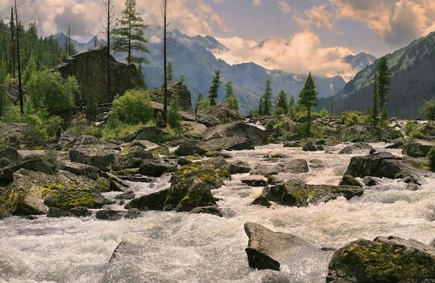 山に沈む夕日を背景にした嵐の山の川