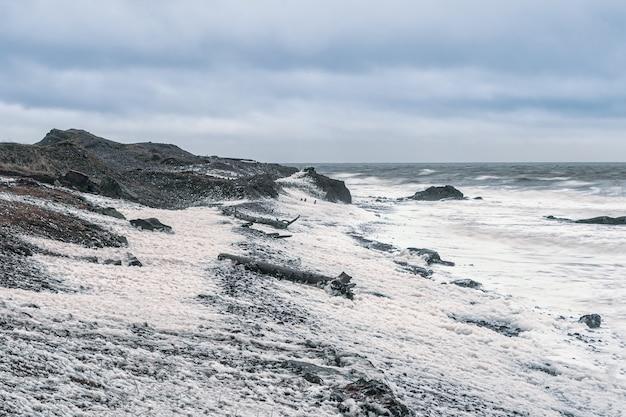 嵐の海。白い泡の波が岩の多い海岸を転がります。白海。