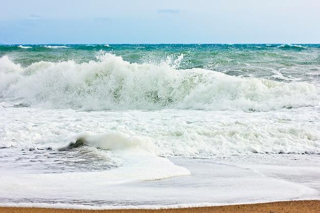 Stormy sea and blue sky, white sea foam on a yellow sandy beach.