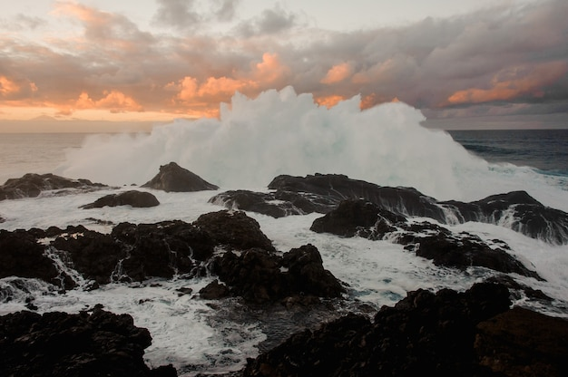 Stormy sea wave and a lot of rocks under the cloudy sky during sunset on summer evening
