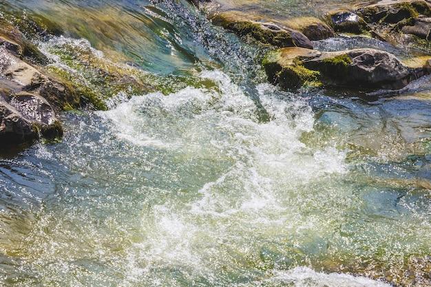 山の川の小石の近くの嵐の水の流れ