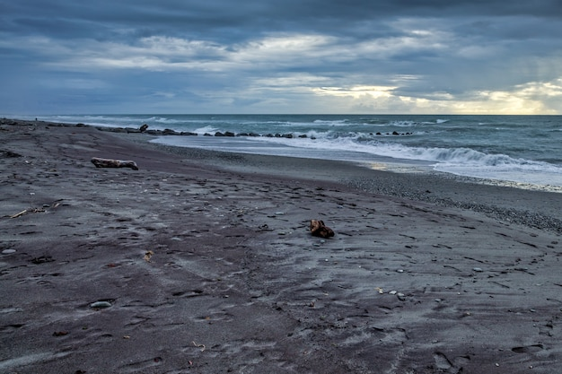 Штормовая погода приближается к пустынному пляжу в новой зеландии