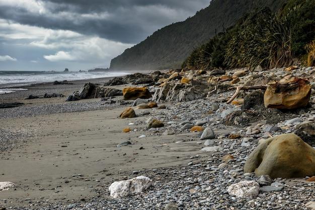 Штормовая погода приближается к усыпанному камнями пляже в новой зеландии