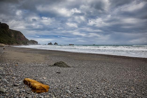 Штормовая погода приближается к оранжевой скале на пляже в новой зеландии