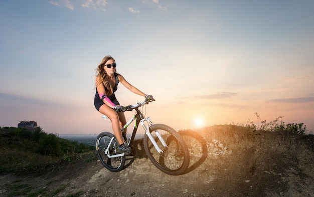 Storty pretty woman riding on the mountain bicycle on a trail on the sunset