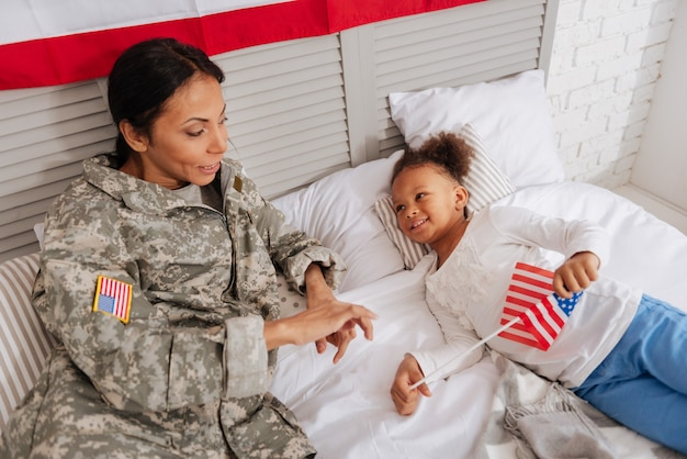 Storytelling time. determined passionate brave woman telling her daughter interesting stories from her service after returning home from training camp and enjoying her vacation