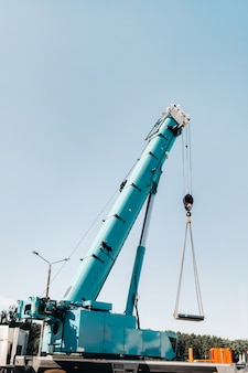The stove is loaded onto a large blue car crane and prepared for operation .