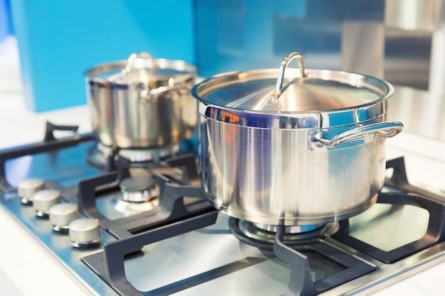 Плита с кастрюлей на белой современной кухне