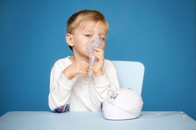 Strabismus boy doing inhalation with a nebulizer on a blue