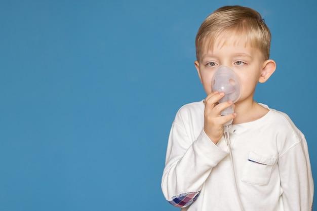 A strabismus boy doing inhalation with a nebulizer