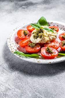Stracciatella on small plate served with fresh tomatoes and basil.