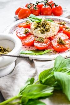 Stracciatella на маленькой тарелке подается со свежими помидорами и базиликом.