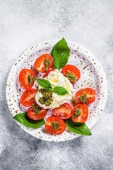 Итальянский сыр stracciatella (буррата) на маленькой тарелке, подается со свежими помидорами и базиликом. серый фон пространство для текста.