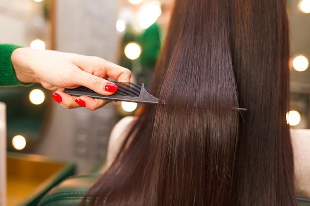 라미네이션 후 똑 바르고 빛나는 머리카락. 미용사는 각질 머리 교정의 결과를 보여줍니다