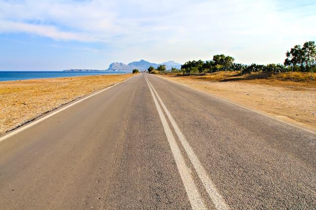 Straight asphalt road along the sea on the greek island of rhodes