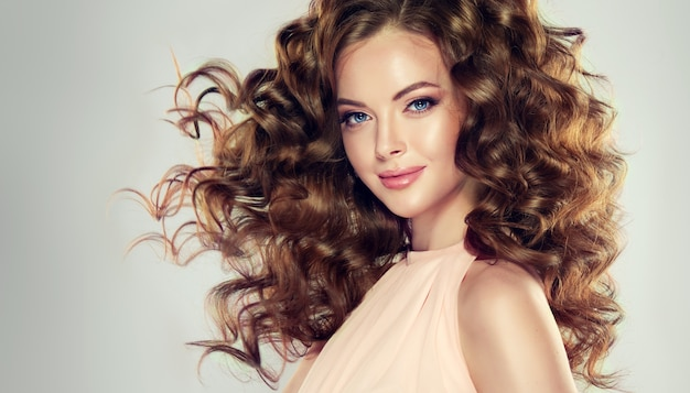 Straight look of beautiful blue eyes.model with wavy, dense and lush hairstyle and tender smile on her lips.