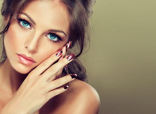 見る人に美しい青い目をまっすぐに見ます。金色のマニキュアが施された細い指が、イブニングメイクをした若い女性の魅力的な顔に触れています。グラマースタイル。