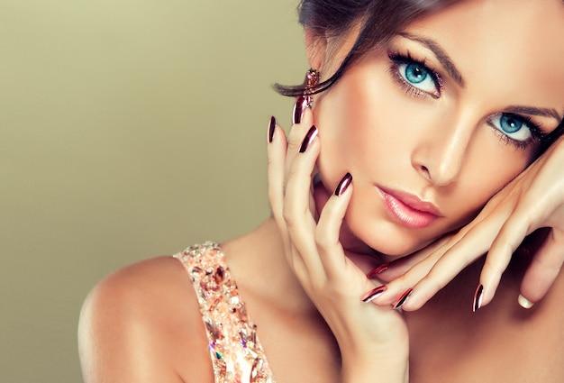 Прямой взгляд красивых голубых глаз на зрителя. тонкие пальцы с позолоченным маникюром трогают привлекательное лицо молодой женщины, одетой в вечерний макияж. гламурный стиль.