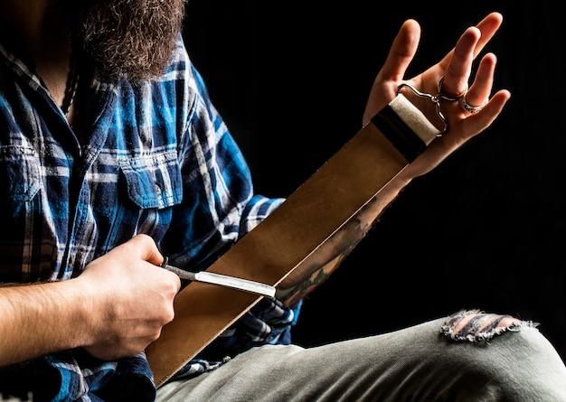 Ручная бритва. винтажные инструменты для парикмахеров, бритва, лезвие для заточки кожи, щетка, бритвенные лезвия. человек поправляет опасную бритву кожаным инструментом.