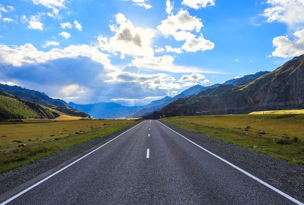 まっすぐな道は山々を背景に地平線に行くアルタイ山脈シベリアロシア