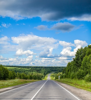Straight road with a marking on the nature background. open road in future, no cars, auto on asphalt road through green forest, trees. clouds on blue sky in summer, sunshine, sunny day. bottom view