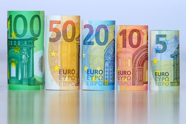 Straight row of accurately rolled hundred, fifty, twenty, ten and five new paper euro banknotes isolated on white. symbol of financial prosperity, wealth, success, savings and business.