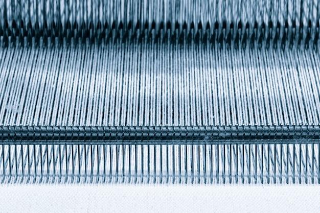 Фон текстуры прямых нитей, швейное оборудование, ткацкое оборудование на швейной фабрике