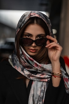 Straightens fashion sunglasses. portrait sexy girl model in stylish black coat with vintage silk scarf on head posing on the city near the road.