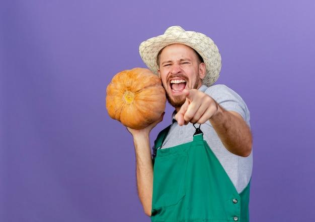긴장과 자신감이 젊은 잘 생긴 슬라브 정원사 유니폼과 모자 한 손으로 butternut 호박을 들고 찾고 복사 공간이 보라색 벽에 고립 가리키는