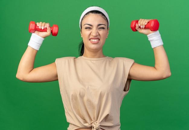 Giovane donna sportiva caucasica tesa che indossa fascia e braccialetti guardando i manubri di sollevamento anteriori isolati sulla parete verde