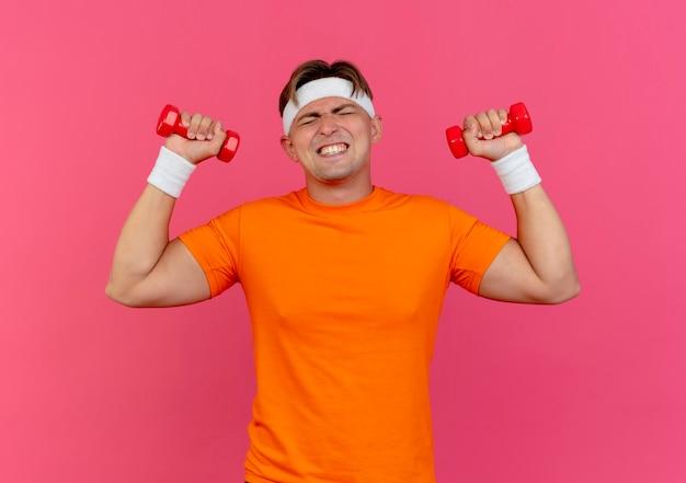 머리띠와 분홍색 벽에 고립 된 닫힌 눈으로 아령을 올리는 팔찌를 착용하는 긴장된 젊은 잘 생긴 스포티 한 남자