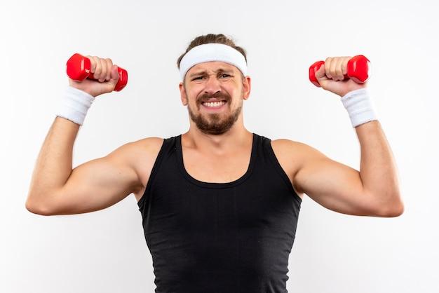 Teso giovane uomo sportivo bello indossando la fascia e braccialetti alzando manubri isolati su uno spazio bianco