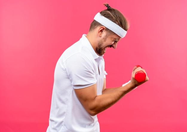 Teso giovane uomo sportivo bello che indossa fascia e braccialetti in piedi in vista di profilo tenendo i manubri con gli occhi chiusi isolati su spazio rosa